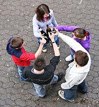 Kinder stehen mit Alkoholflaschn im Kreis und prosten sich zu.