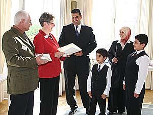 Landrätin Beate Läsch-Weber und Klaus Schmitz überreichen die Einbürgerungsurkunden an die aus dem Irak stammende Familie Said aus Rivenich.