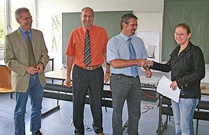 ÜAZ-Geschäftsführer Hartmut Weber überreicht einer der acht Absolventinnen das Zeugnis ihres Hauptschulabschlusses. Zu den Gratulanten zählen auch Hans-Georg Simon von der ARGE Wittlich (l.) sowie  ÜAZ-Lehrer Detlef Wiese (2.v.l.).