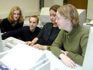 Schülerinnen und Schüler arbeiten  an einem PC.