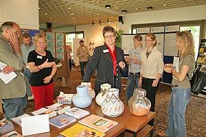 Landrätin Beate Läsch-Weber prüft am Stand des Fachbereichs Gesundheit ihren Tastsinn und greift in einen Tonkrug.