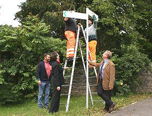 Landrätin Beate Läsch-Weber und der Leiter der Straßenmeisterei Wittlich, Ralf Schmitz bei der symbolischen Schildbefestigung am Kloster Machern.