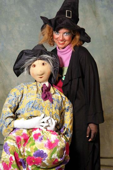 Schauspielerin in Hexenkostüm mit lebensgroßer Puppe