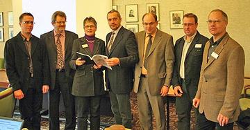 Landrätin Läsch-Weber nimmt im Beisein von Vertretern der Fachhochschule Mainz, des Landkreistages und der Kreisverwaltung Bernkastel-Wittlich den Abschlussbericht von Professor Müller (4. v. l.) entgegen.