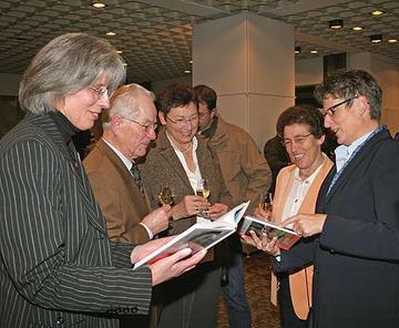 Zur Vorstellung des Kreisjahrbuchs im Kreishaus betrachtet Landrätin Beate Läsch-Weber (r.) gemeinsam mit Redaktionsleiterin Claudia Schmitt (l.) und weiteren Autorinnen und Autoren das druckfrische Werk.