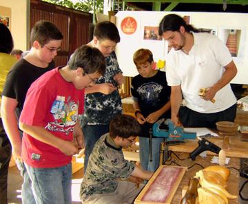 Ein Betreuer zeigt Kindern die Werkstätten.