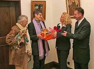 Unter den Augen der ältesten Päckchenpackerin Johanna Justen (1. v. l) und dem Leiter der Sammelstelle Wittlich, Bruder Nikolaj Bromberg (4. v. l.), gibt Landrätin Läsch-Weber (2. v. l.) ihr persönliches Päckchen der Regionalleiterin Evelyne Reinhar