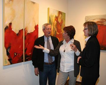 Meggi Fritzen erläutert Maria Bernard und Burkhard Okfen eines ihrer Werke, das zur Zeit in der Kreisverwaltung in Wittlich ausgestellt ist.