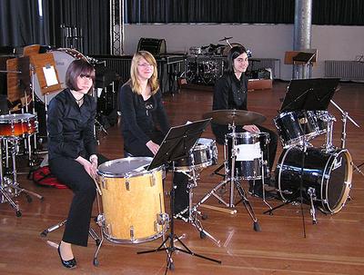 Das Schlagzeugtrio Viktoria Schomer, Sandra Hofer und Leonie Klein an ihren Trommeln sitzend.