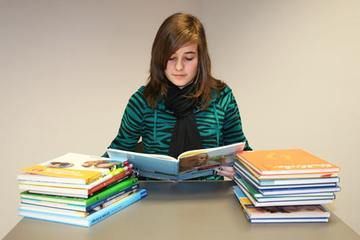 Schülerin hinter einem Berg von Schulbüchern.
