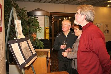 Besucher der Ausstellungseröffnung im Kreishaus betrachten die erste fotografische Aufnahme der Stadt Wittlich aus dem Jahr 1856.