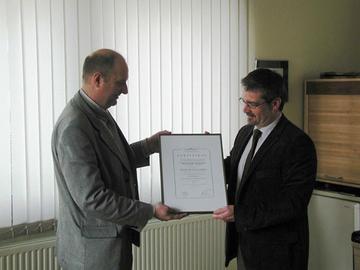 Überreichung des Zertifikates durch den Qualitäts-Management-Beauftragten Detlef Wiese (l.)an den Geschäftsführer des ÜAZ-Wittlich Hartmut Weber (r.).