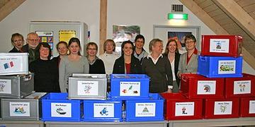 Landrätin Beate Läsch-Weber, die Leiterin der Kreisergänzungsbücherei Anke Freudenreich, Mitarbeiterinnen der Stadtbücherei Wittlich und Lehrkräfte hinter den Medienboxen stehend.