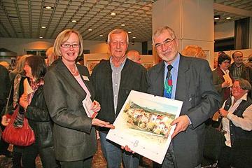 Zur Ausstellungseröffnung überreichte Burkhard Okfen (m.) an Otto Mixa (r.) einen Kalender mit Aquarellen als Dank für seine in Versform gehaltene Hommage. Ebenfalls im Bild: Geschäftsbereichsleiterin Maria Bernard (l.).
