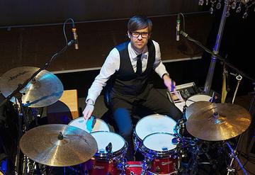 Portraitfoto des Schlagzeugers hinter seinem Drumset