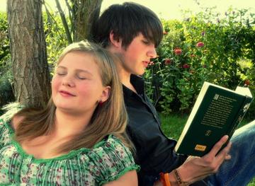 Junge liest Mädchen aus einem Buch vor.