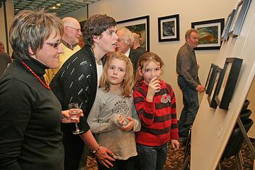 Erwachsene und Kinder betrachten Werke von Heike Hooghoff in der Ausstellung.